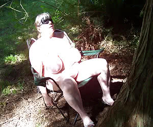 Mature nudists in their home garden