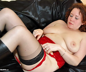 Horny redhead Jessica dressed in red lingerie is stripping nude and starts masturbating with one of her dildo sex toys.