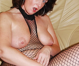 Manuela, horny mature milf wearing high heel shoes and a crotchless fishnet body-stocking. Manuela enjoys spreading her